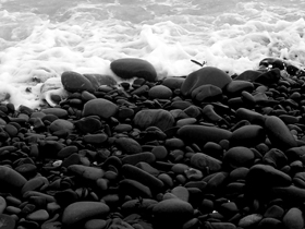 dark pebbles and white sea foam
