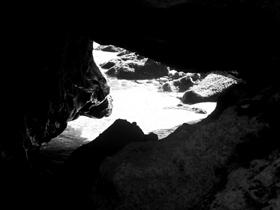 tiny bright beach through dark rocks