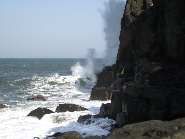Waves splashing high against cliff at Morgan Bay