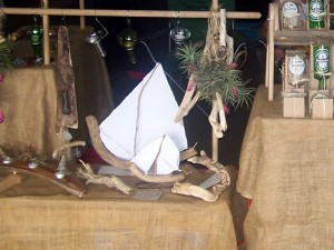 big and small driftwood yachts, loose driftwood pieces, hanging bottle neck votive candle holders, glasses cut from beer bottles